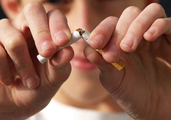 Zwei Hände brechen Zigarette in der Mitte auseinander
