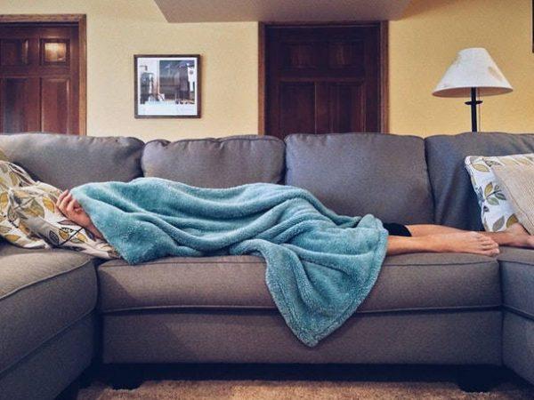 Jemand schläft unter der Decke auf Schlafsofa in Wohnung