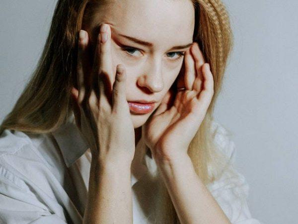 Frau massiert sich die Schläfen am Kopf